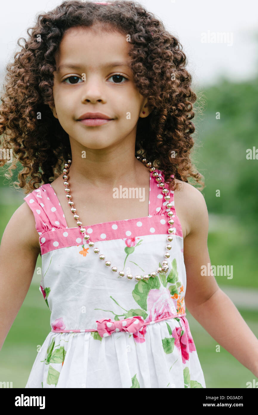 Young Girl With Curly Brown Hair Wearing Summer Dress and Necklace, Portrait - Stock Image