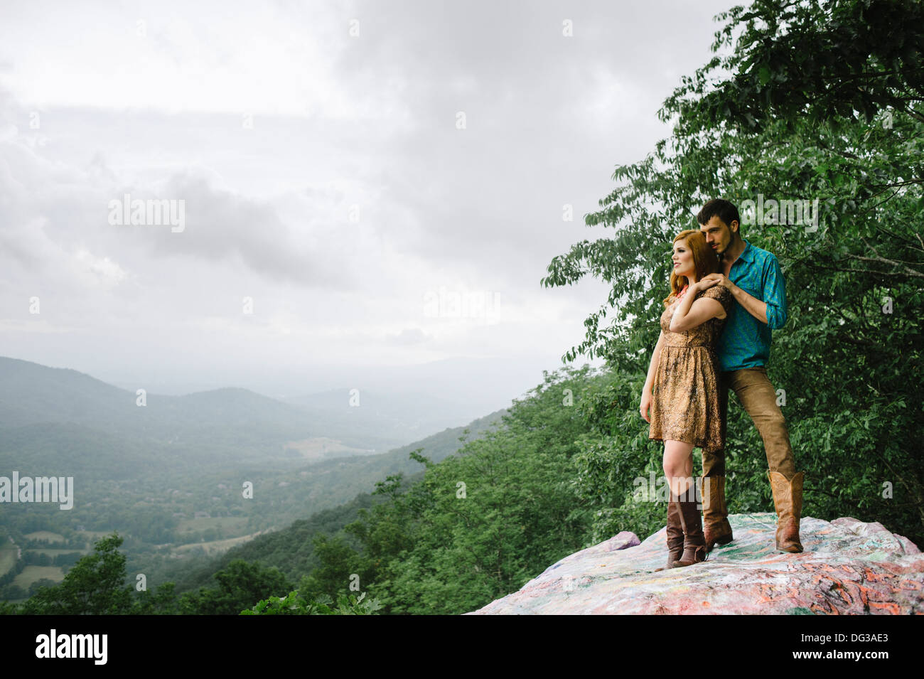 Young Couple Standing on Rock Ledge While Enjoying Scenic View - Stock Image