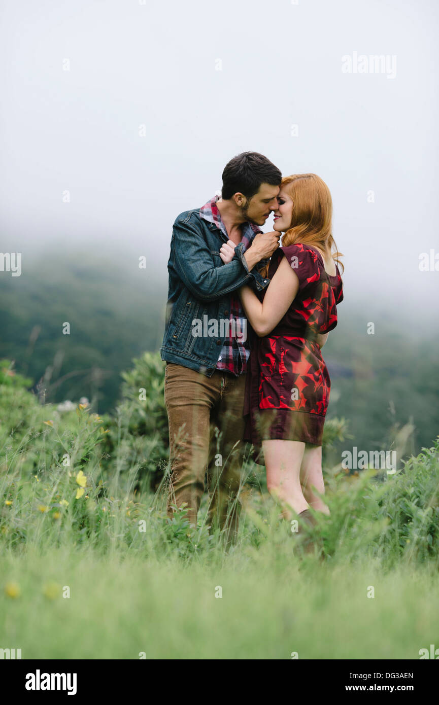 Romantic Couple About to Kiss in Foggy Field - Stock Image