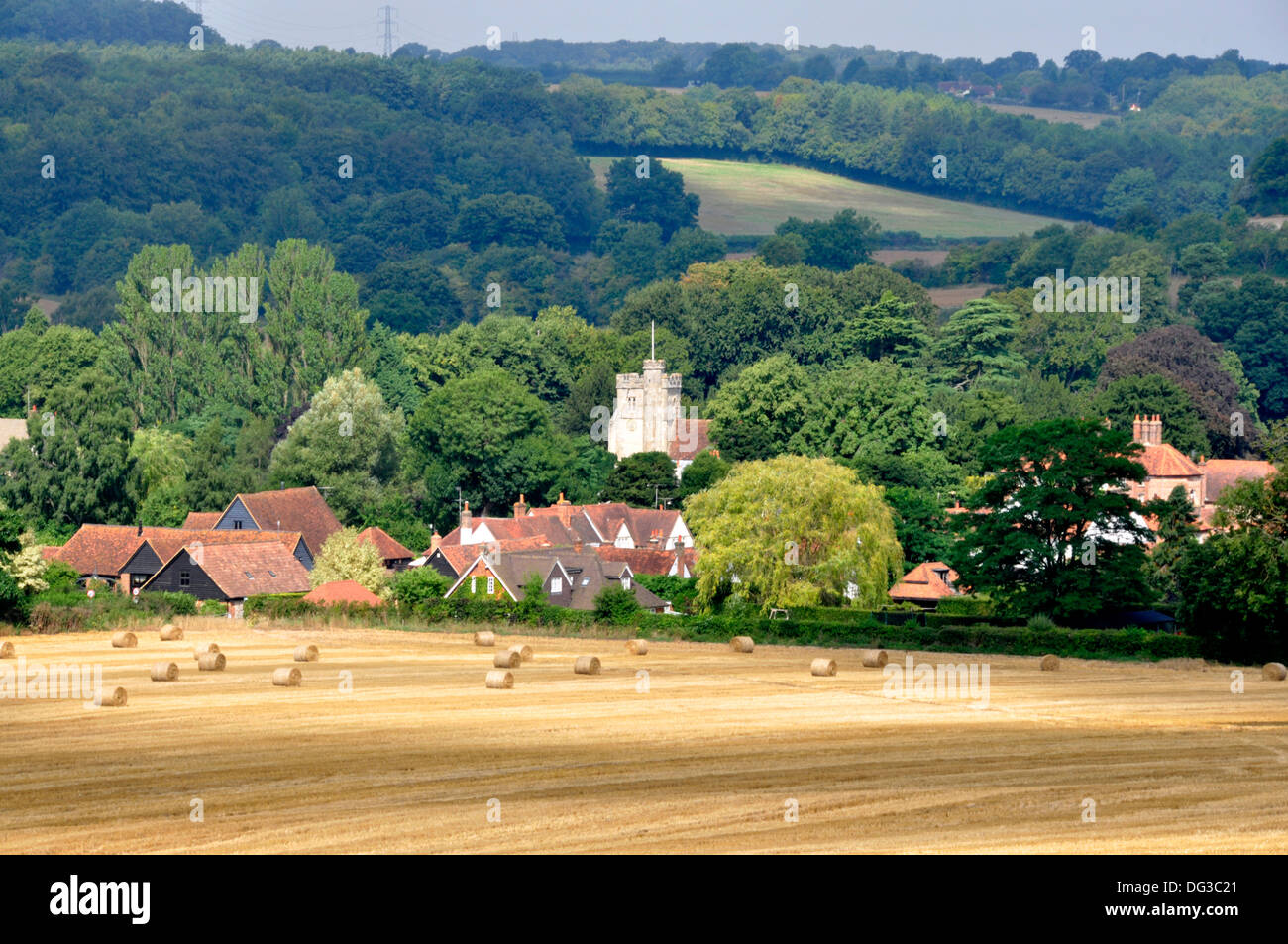 Bucks - Chiltern Hills -view to Little Missenden village - over field of golden stubble - straw baled for collection - sunlight - Stock Image