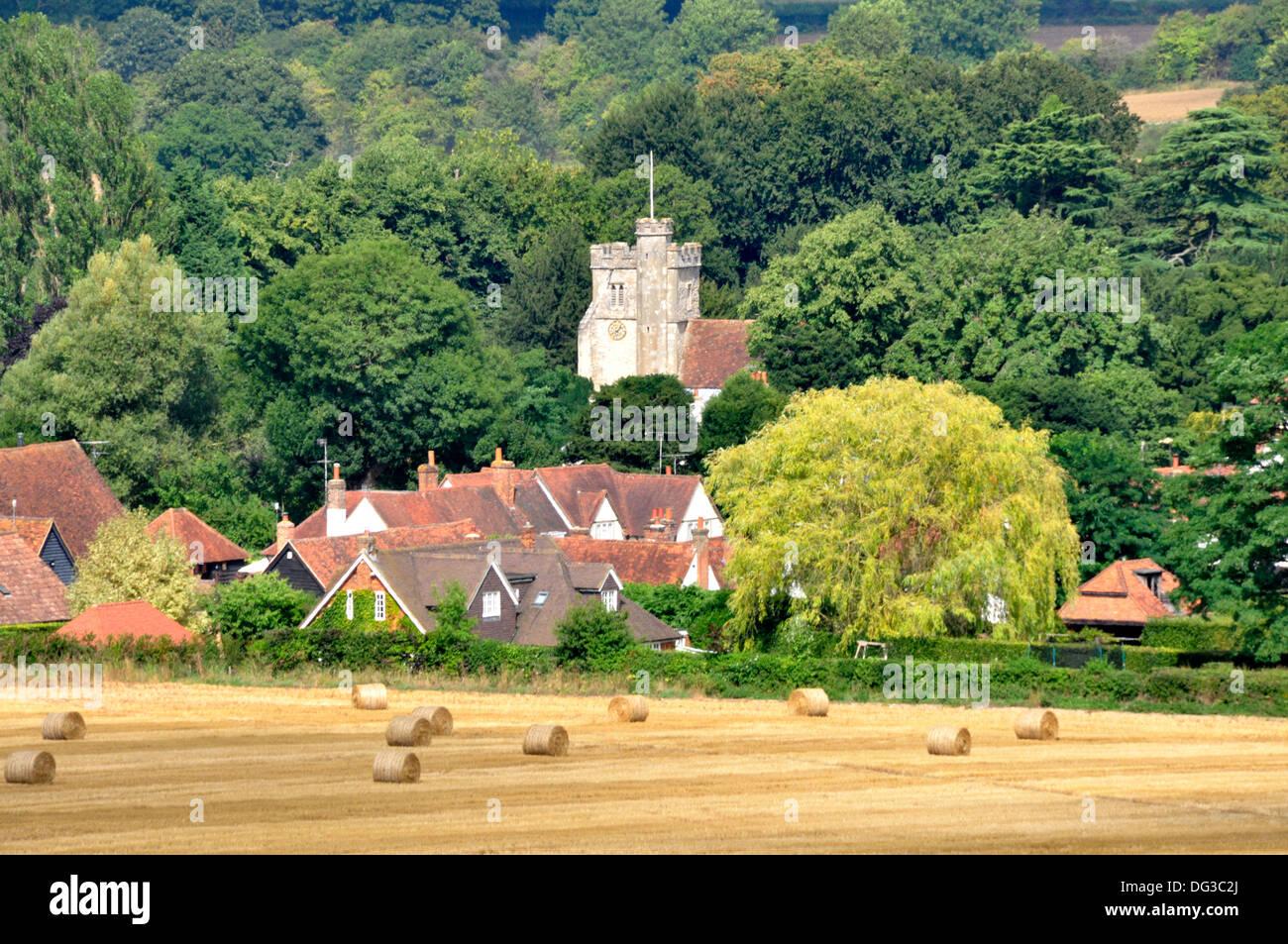 Bucks - Chiltern Hills - Little Missenden - after the harvest - bales of straw - golden stubble - village backdrop - sunlight - Stock Image
