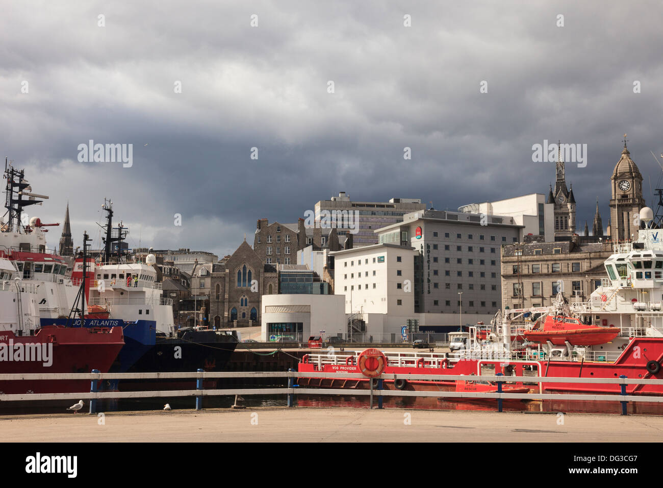City centre buildings and Ibis Hotel from port with North Sea offshore supply ships in dock in Aberdeen Scotland UK - Stock Image