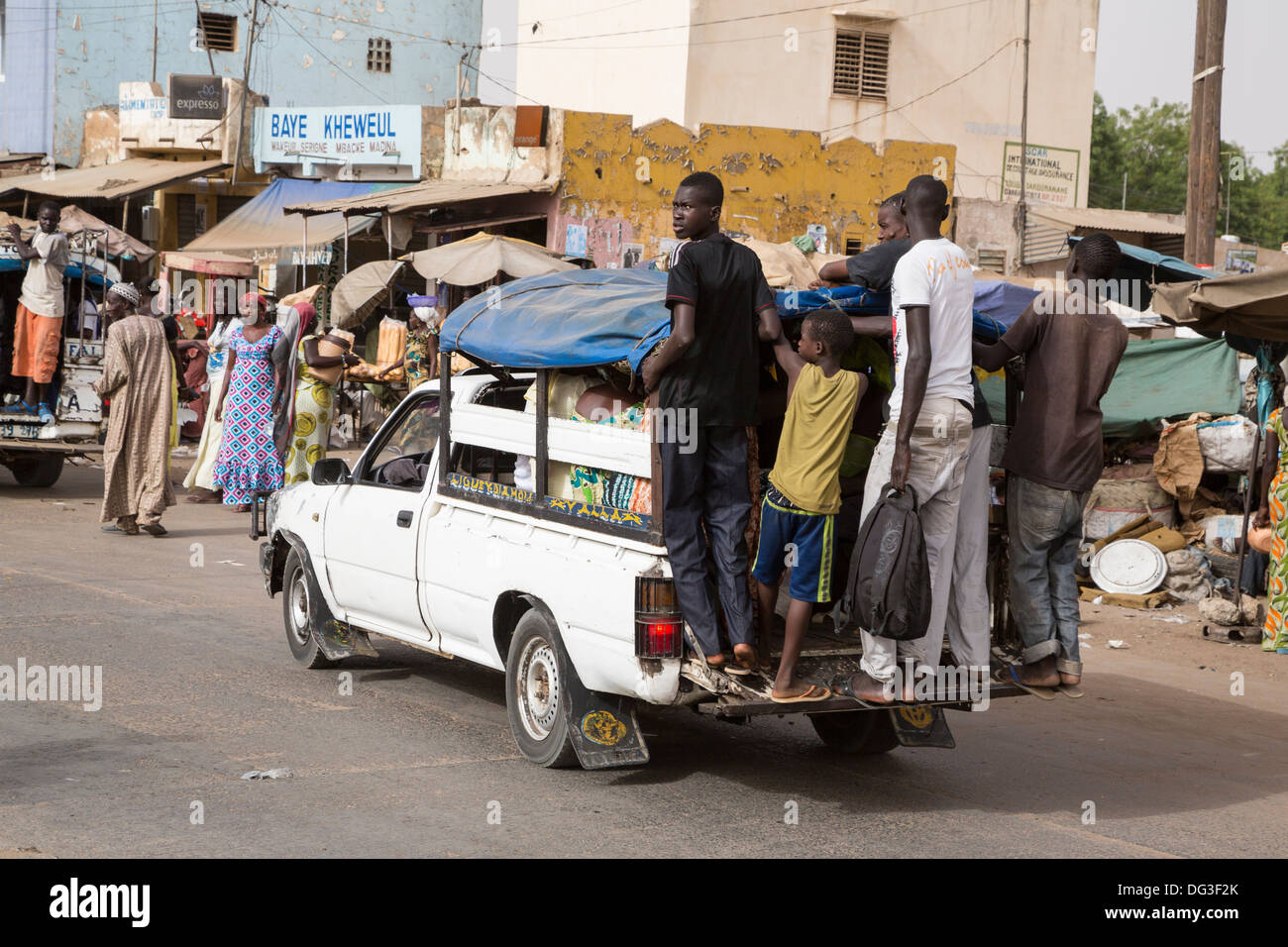 Senegal, Touba. Local Transport. Pick-ups with Young Men usually Hanging on the Back Running Board, Passengers Inside. - Stock Image