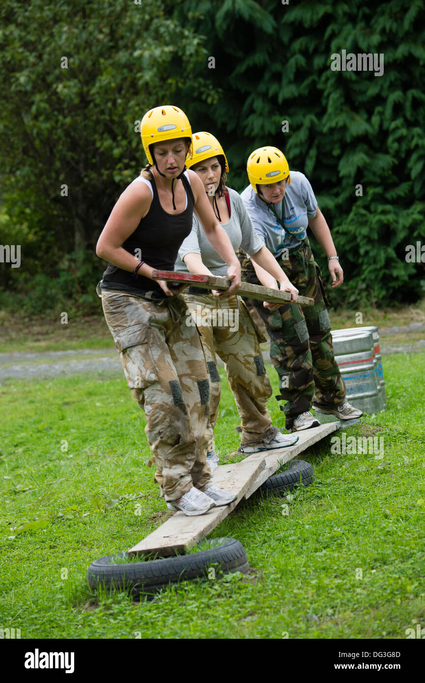 A group of adult women on a team building  teambuilding exercise  problem solving outdoor pursuits workshop event UK - Stock Image