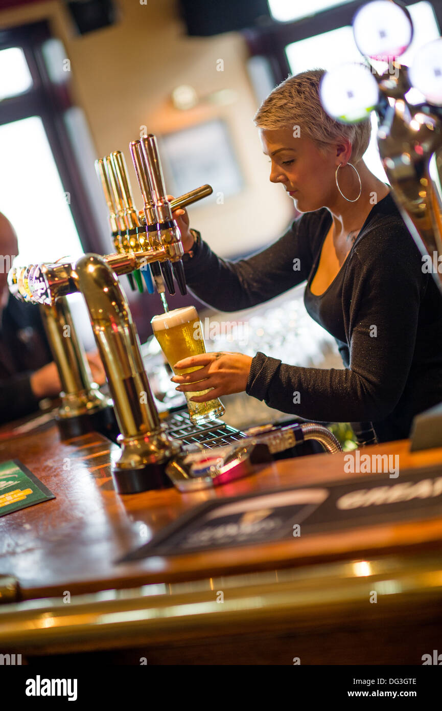 A young woman female barmaid bar worker pouring pulling a pint of lager beer in a pub inn UK - Stock Image