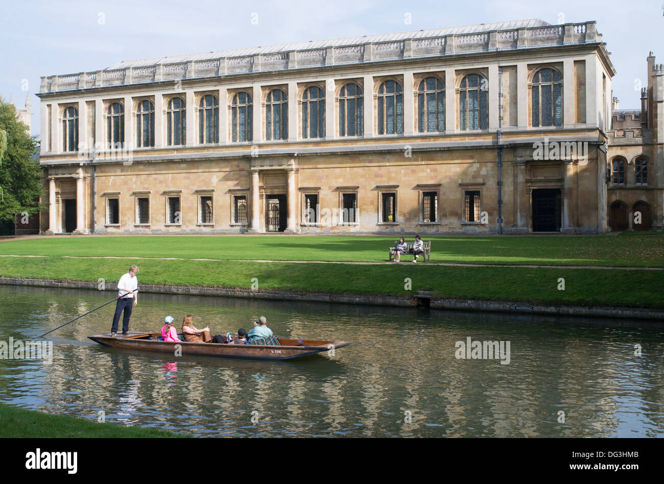 Punt with tourists passing the Wren library of Trinity College University of Cambridge, England, UK - Stock Image