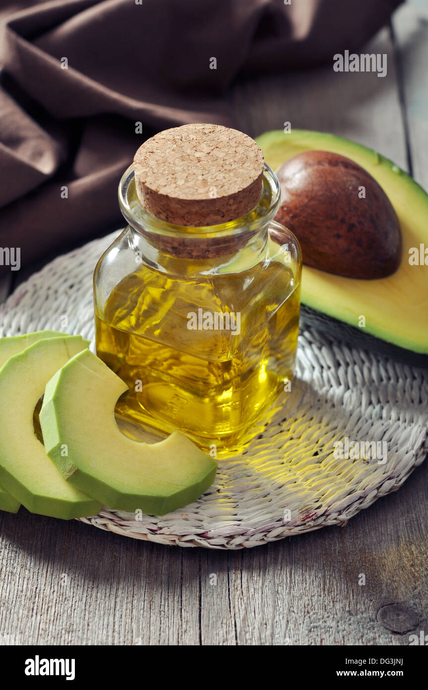 Bottle of avocado essential oil with fresh avocado fruit closeup - Stock Image