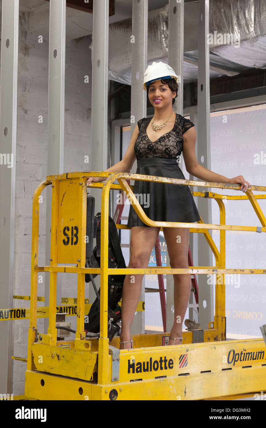 Woman standing on scissor lift at construction site - USA - Stock Image