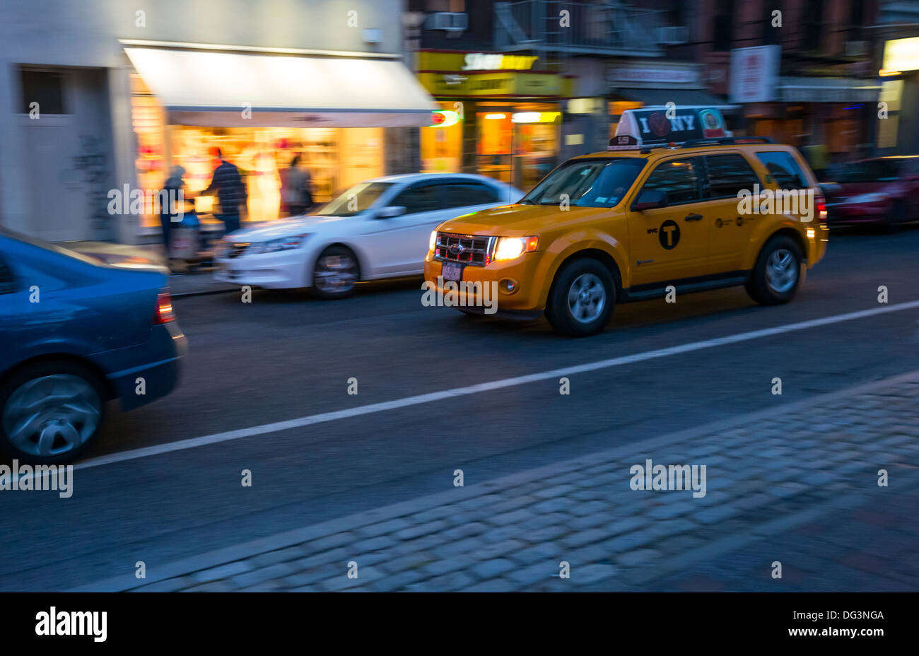 Yellow taxicab in New York City at night - Stock Image
