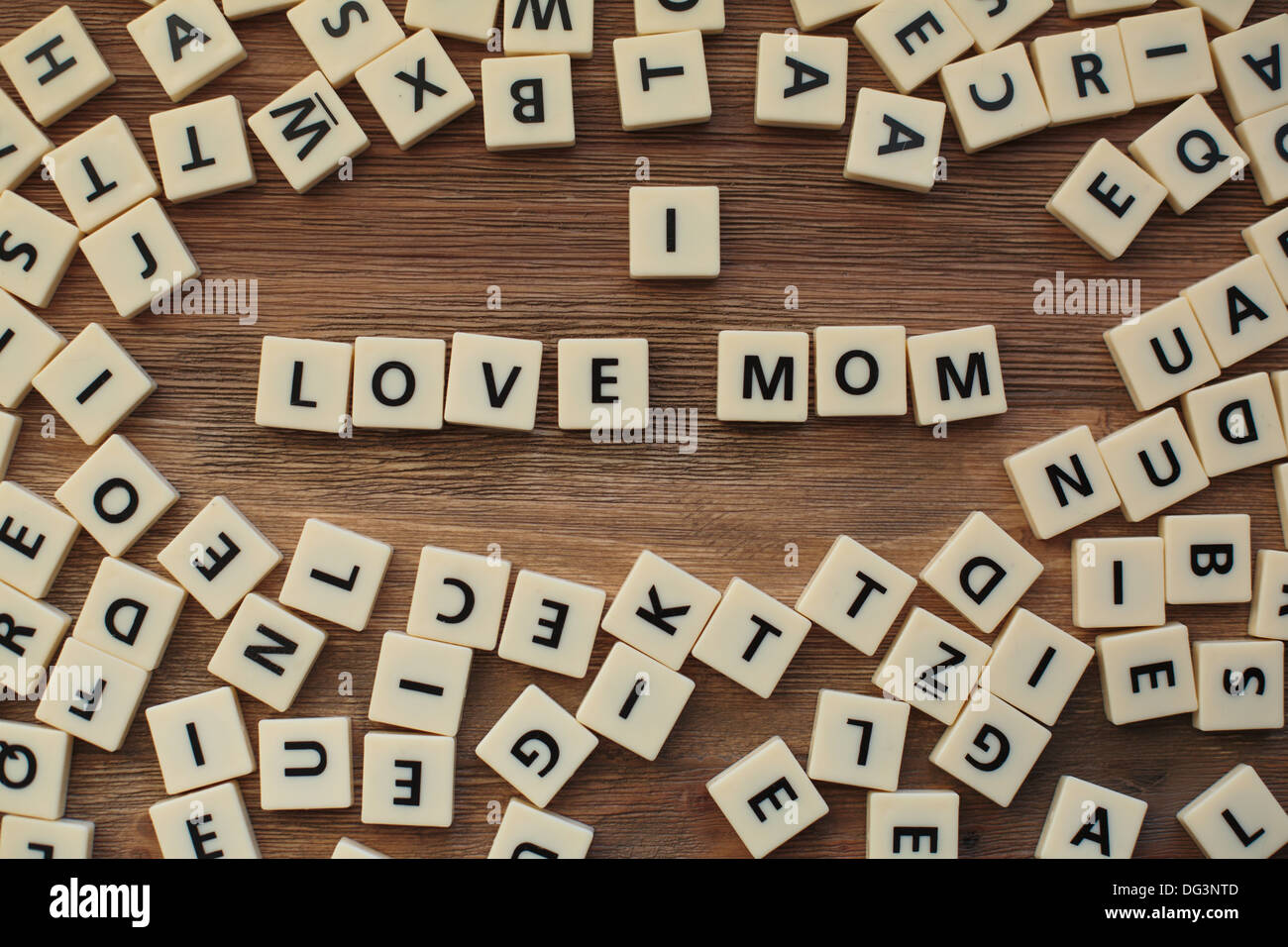 Plastic letters from a childrens' spelling game on a wooden table spell 'I Love Mom' - Stock Image
