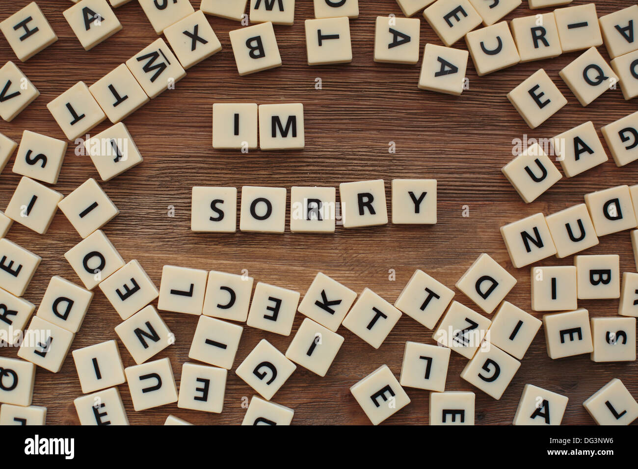 Plastic letters from a childrens' spelling game on a wooden table spell 'I'm Sorry' - Stock Image
