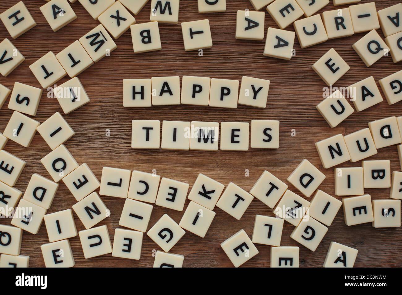 Plastic letters from a childrens' spelling game on a wooden table spell 'happy times' - Stock Image