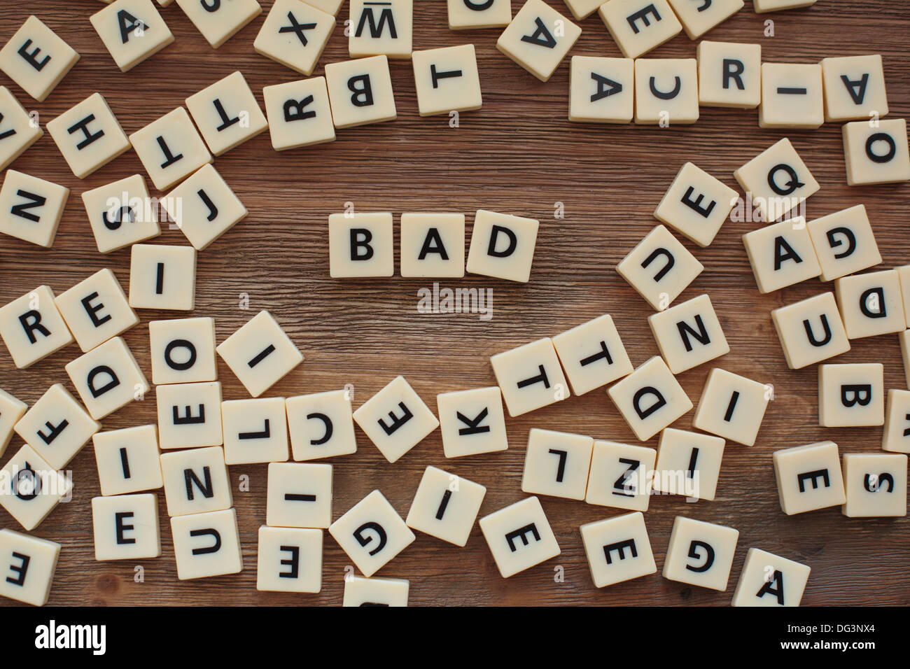 "Plastic letters from a childrens' spelling game on a wooden table spell the word ""bad"" Stock Photo"