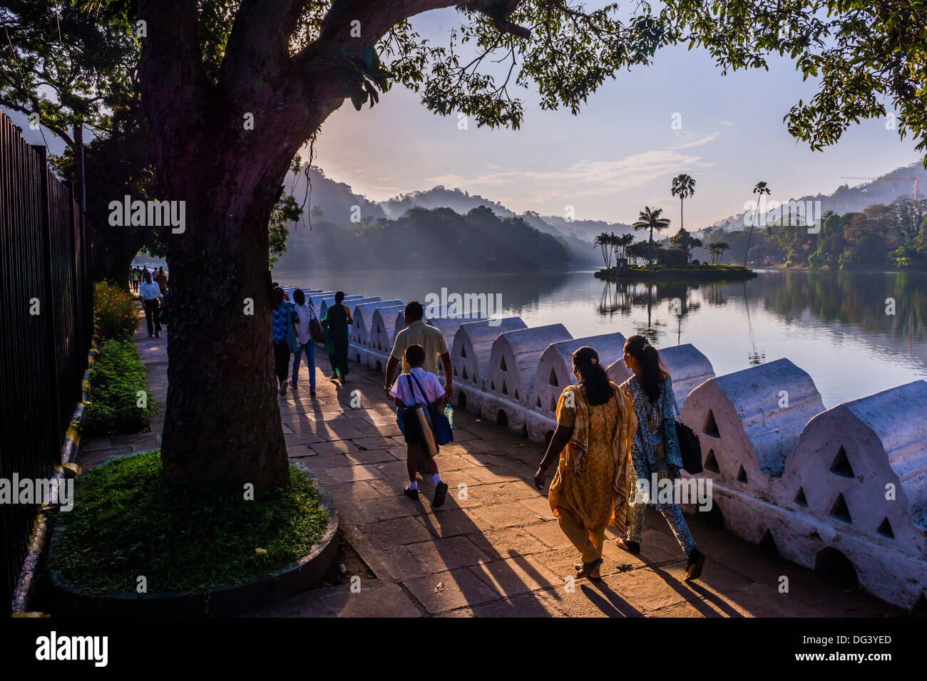 Sri Lankan people walking at Kandy Lake at sunrise, Kandy, Central Province, Sri Lanka, Asia - Stock Image