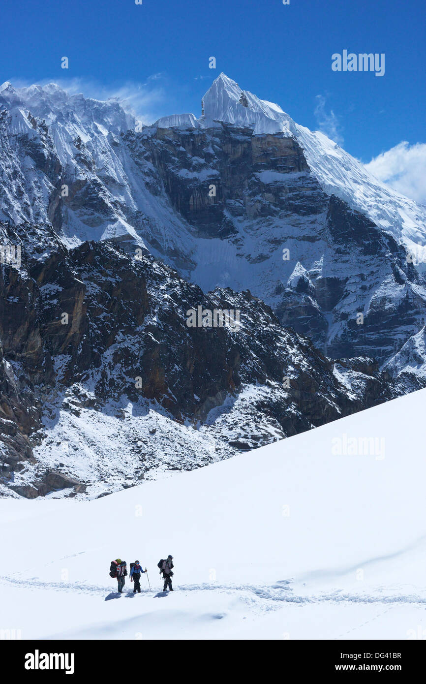 Trekkers crossing glacier on Cho La Pass, with peak of Lobuche East behind, Sagarmatha National Park, UNESCO, Nepal, Himalayas - Stock Image
