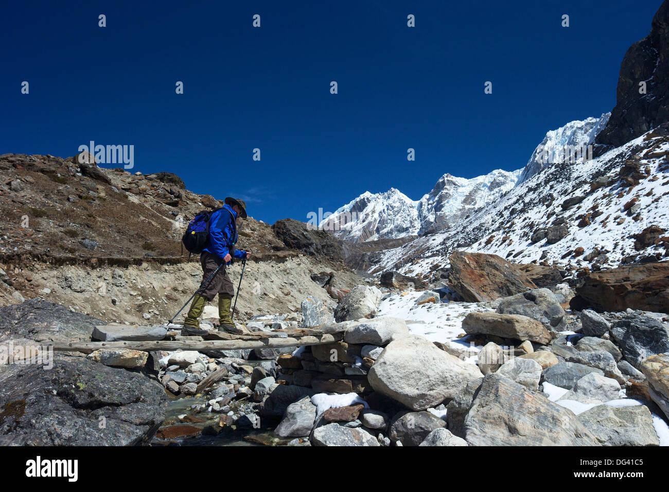 Trekker crossing the Chola Khola valley near Dzonglha, Sagarmatha National Park, UNESCO Site, Nepal, Himalayas - Stock Image