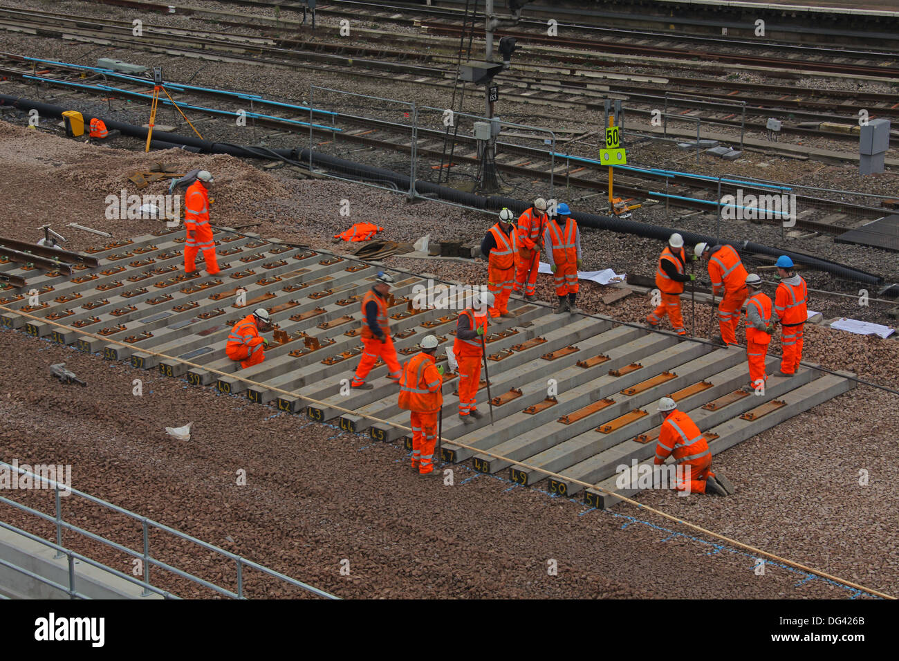Workers installing concrete sleepers for a new set of crossover pointwork being installed in Reading station during the rebuild. - Stock Image