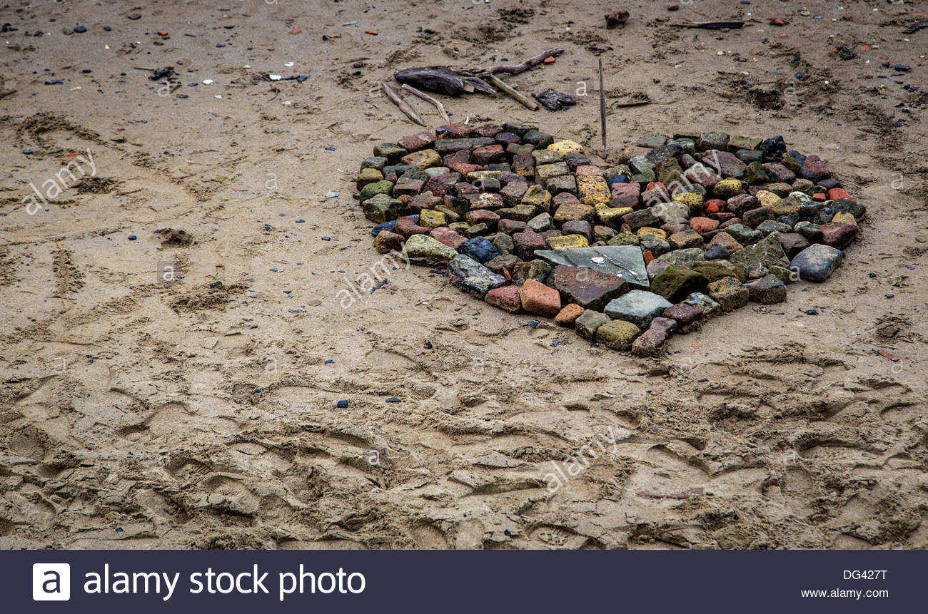 Heart made from stone, rock and debris on the beach at Blackfriars in London - Stock Image