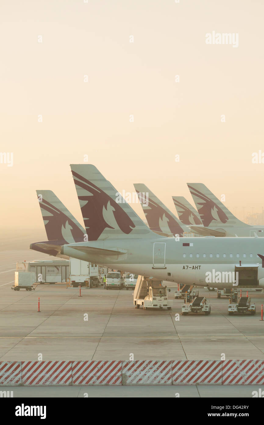Qatar airways planes at Doha airport shortly after sunrise, Qatar - Stock Image
