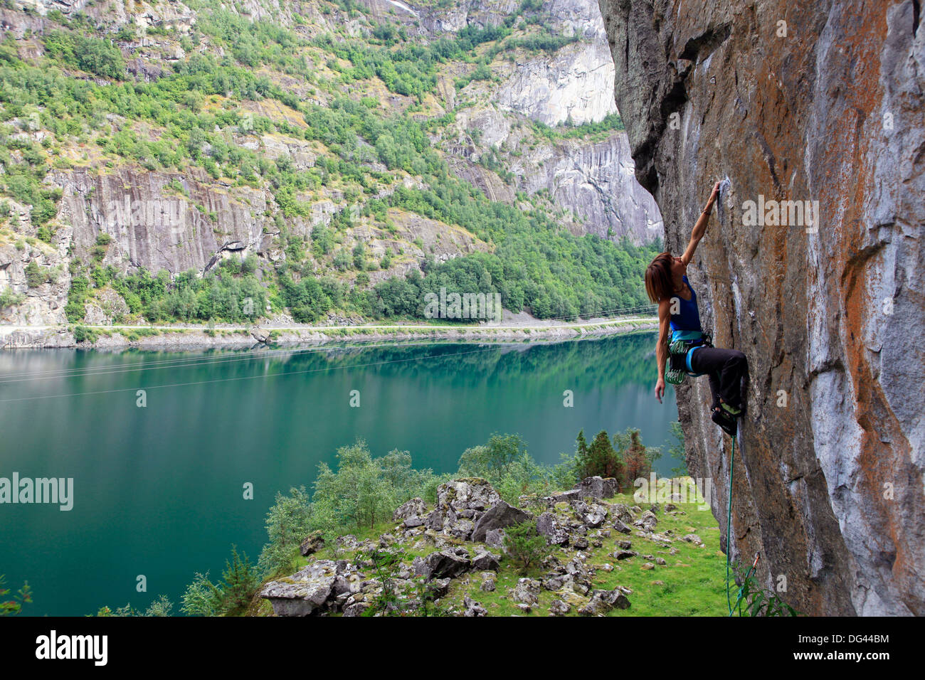 A female climber tackles a steep cliff at Loven, near Aurland, western Norway, Scandinavia, Europe - Stock Image