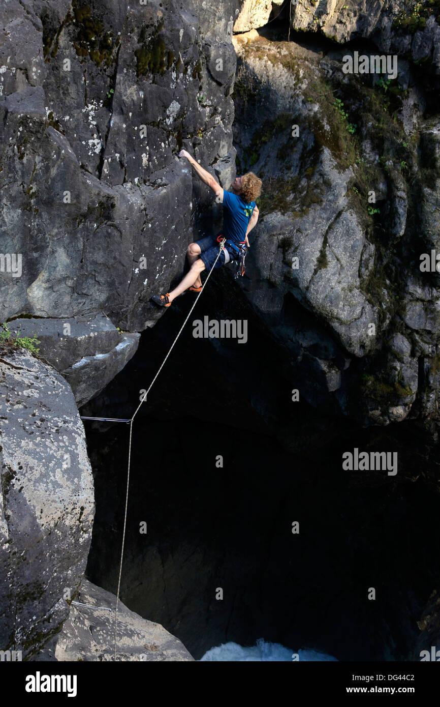 A climber tackles an overhang above Nairn Falls, near Pemberton, British Columbia, Canada, North America - Stock Image