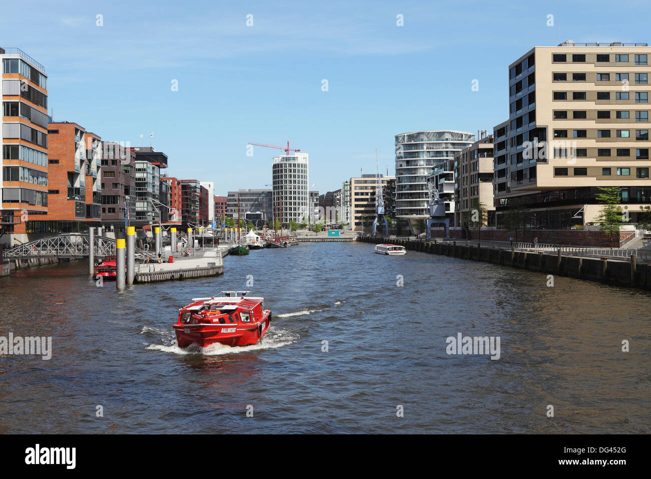 A boat on a canal in the recently developed HafenCity district of Hamburg, Germany, Europe - Stock Image