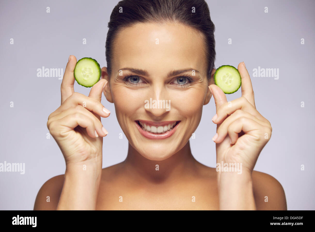 Portrait of young beautiful woman holding cucumber slices in hands near her face smiling at camera on gray background. - Stock Image