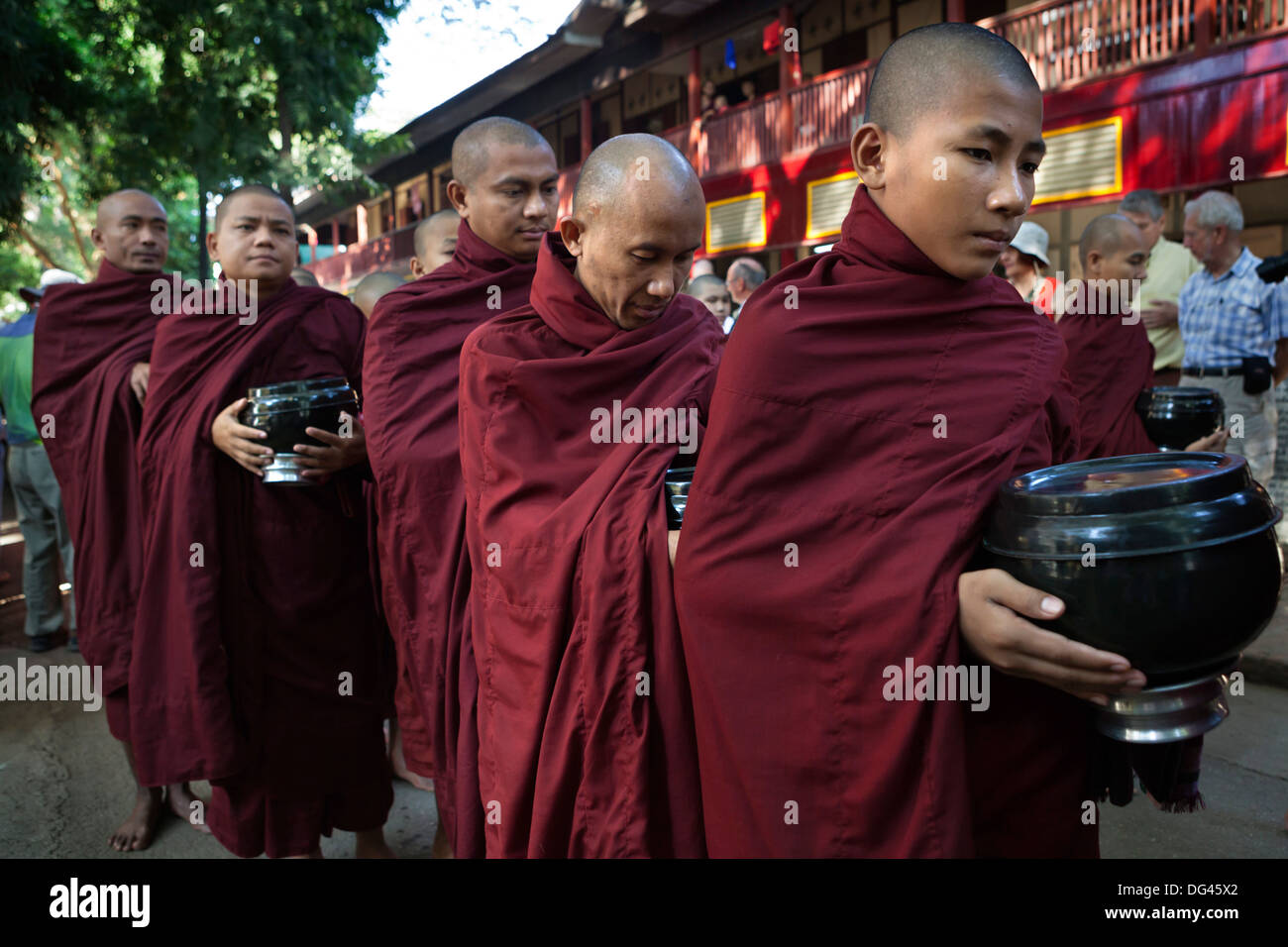Buddhist monks lining up to receive donations of rice for lunch, Mahar Gandar Yone Monastery, Mandalay, Myanmar (Burma), Asia - Stock Image