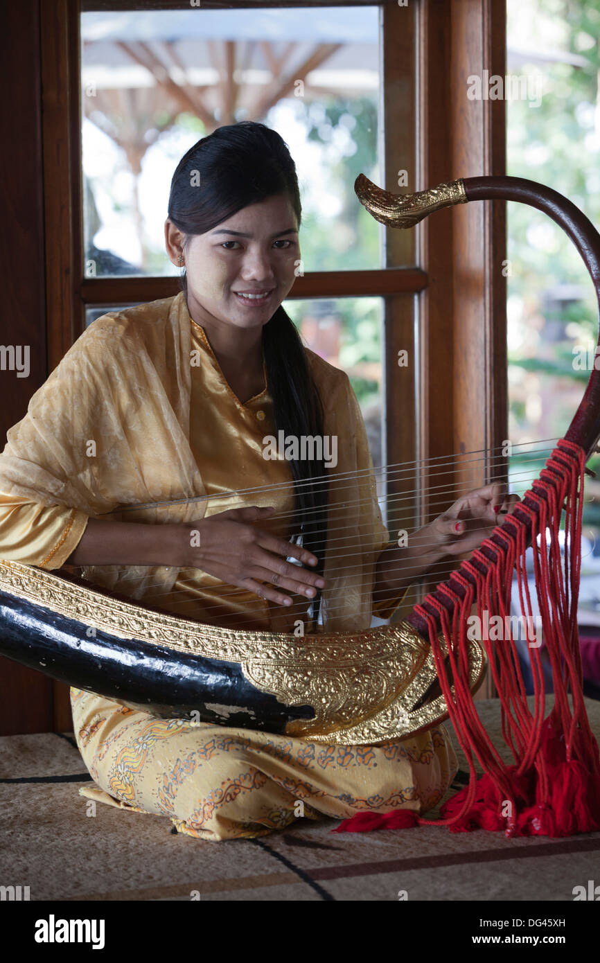 Girl playing traditional saung gauq (boat shaped harp) at Popa Mountain Resort, Mount Popa, near Bagan, Myanmar - Stock Image