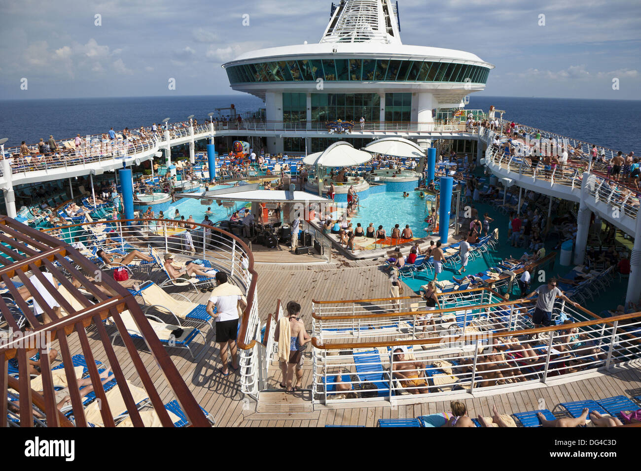 People on deck around swimming pool on Royal Caribbean Navigator of the Seas cruise ship - Stock Image
