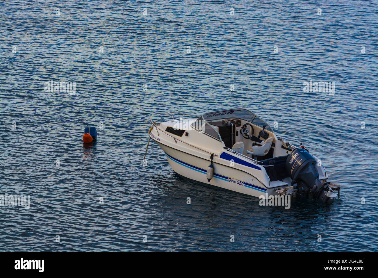 Medium size Marine outboard boat anchored in a bay - Stock Image