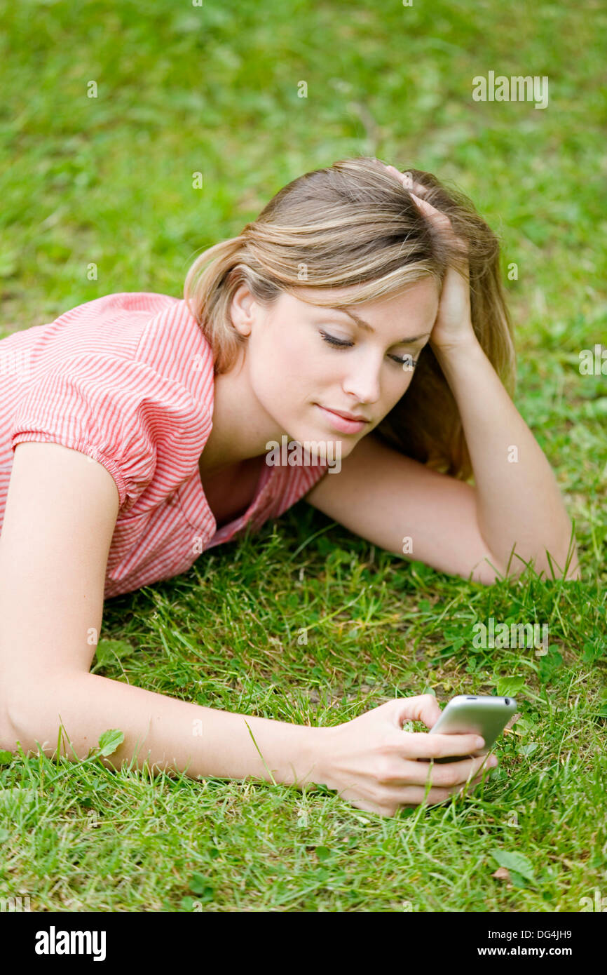 Blonde beautiful woman writting a SMS lying down in the park - Stock Image