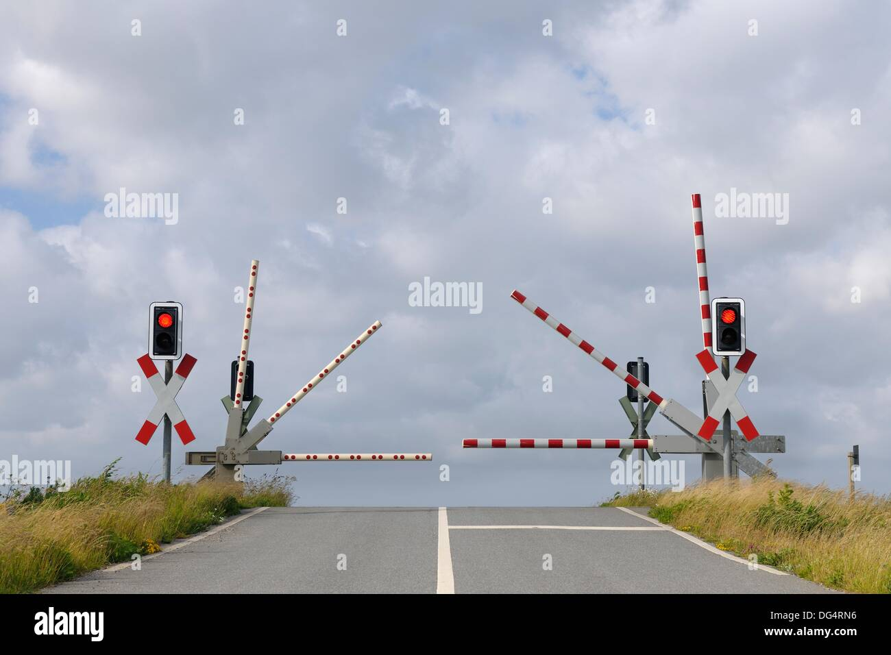 Railroad crossing with gates in motion and traffic lights