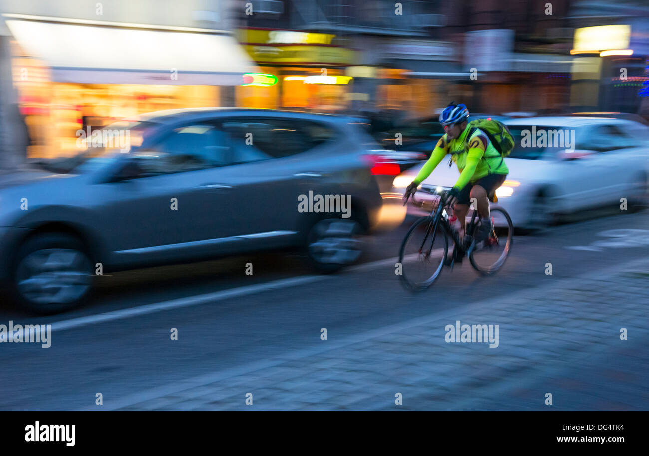 Bicycle rider at night in bike lane in New York City traffic at night - Stock Image