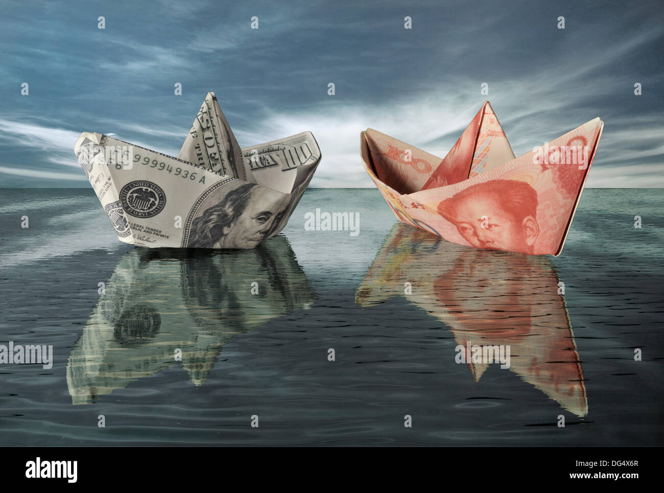 Paper boats of US dollars and Chinese RMBs are facing each other on the high seas. - Stock Image