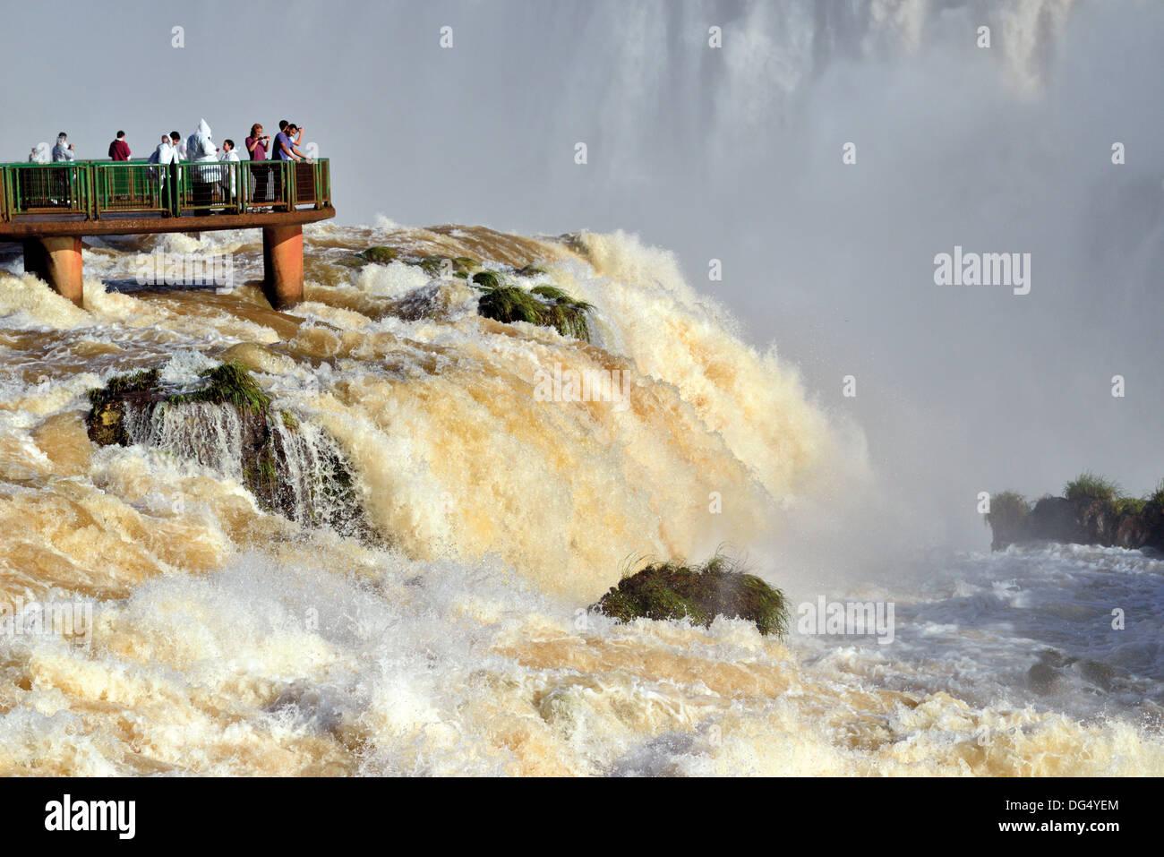 Brazil, Iguassu National Park: Tourists appreciating Iguassu Falls with record water levels from a panorama platform - Stock Image