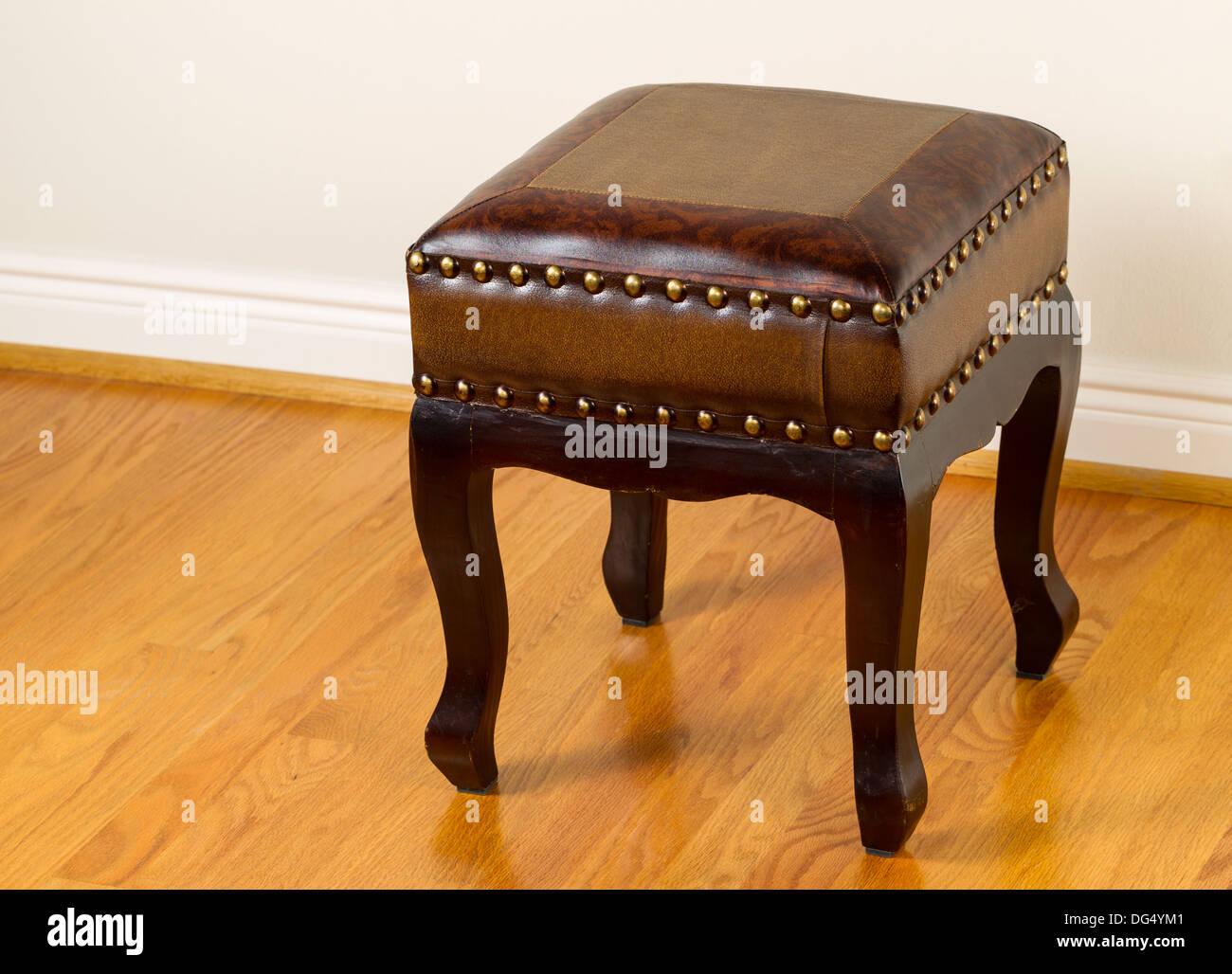 Horizontal photo of padded foot stool on red oak floors - Stock Image