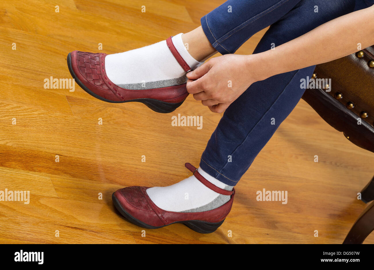 Horizontal photo of woman putting on causal shoes while sitting on leather padded footstool with red oak floors in background - Stock Image