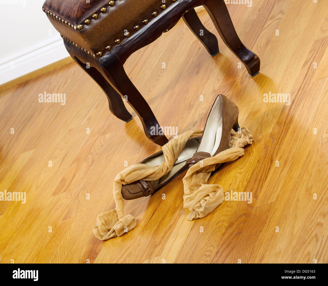 Angled photo of woman stockings and dress shoes lying next to padded footstool with red oak floors in background - Stock Image