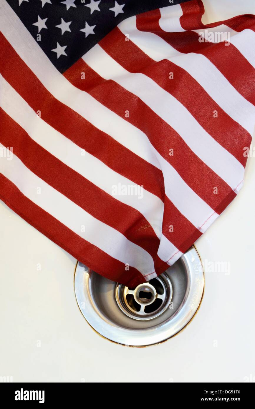American Flag going down the drain  Symbolic image of the decline of the United States  Subtitled: The effect of Liberalism - Stock Image