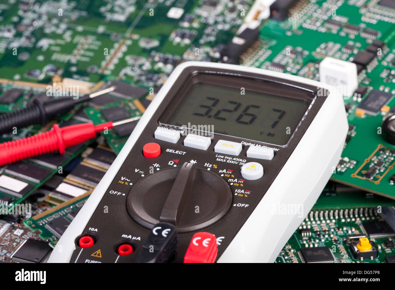 Digital multimeter is lying on many circuit boards - Stock Image