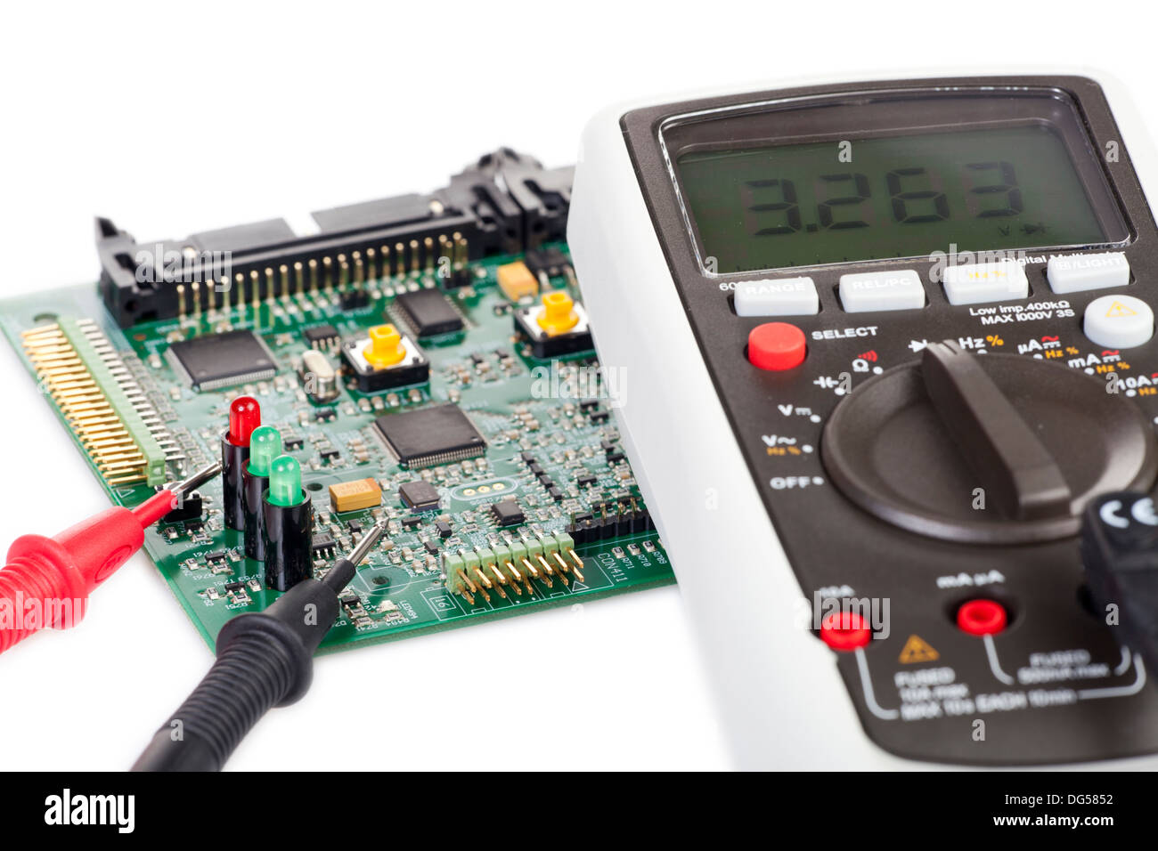 Digital multimeter and a circuit board isolated on white background - Stock Image