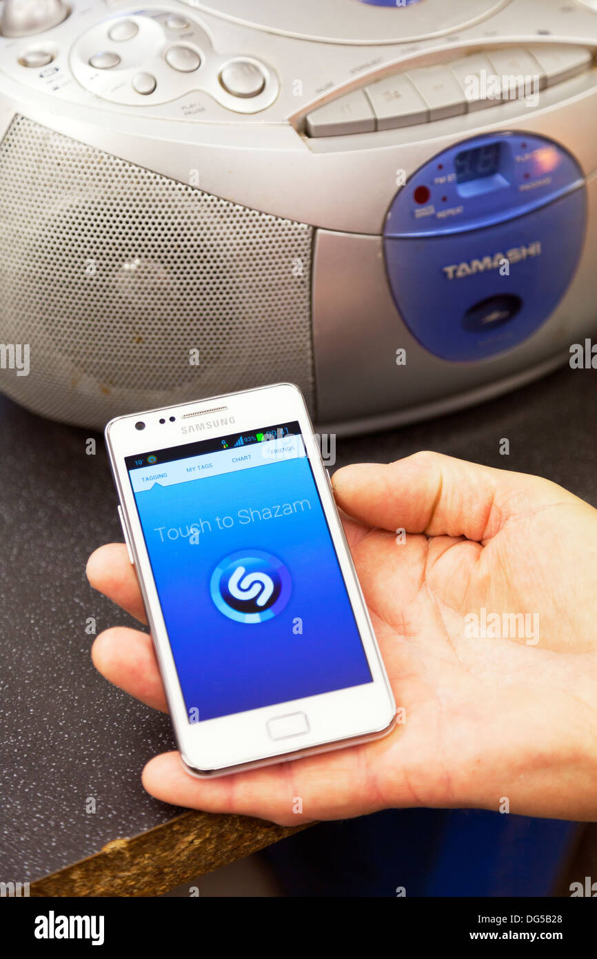 Shazam app application running working on samsung s2 smartphone male hand holding phone interacting with radio listening - Stock Image