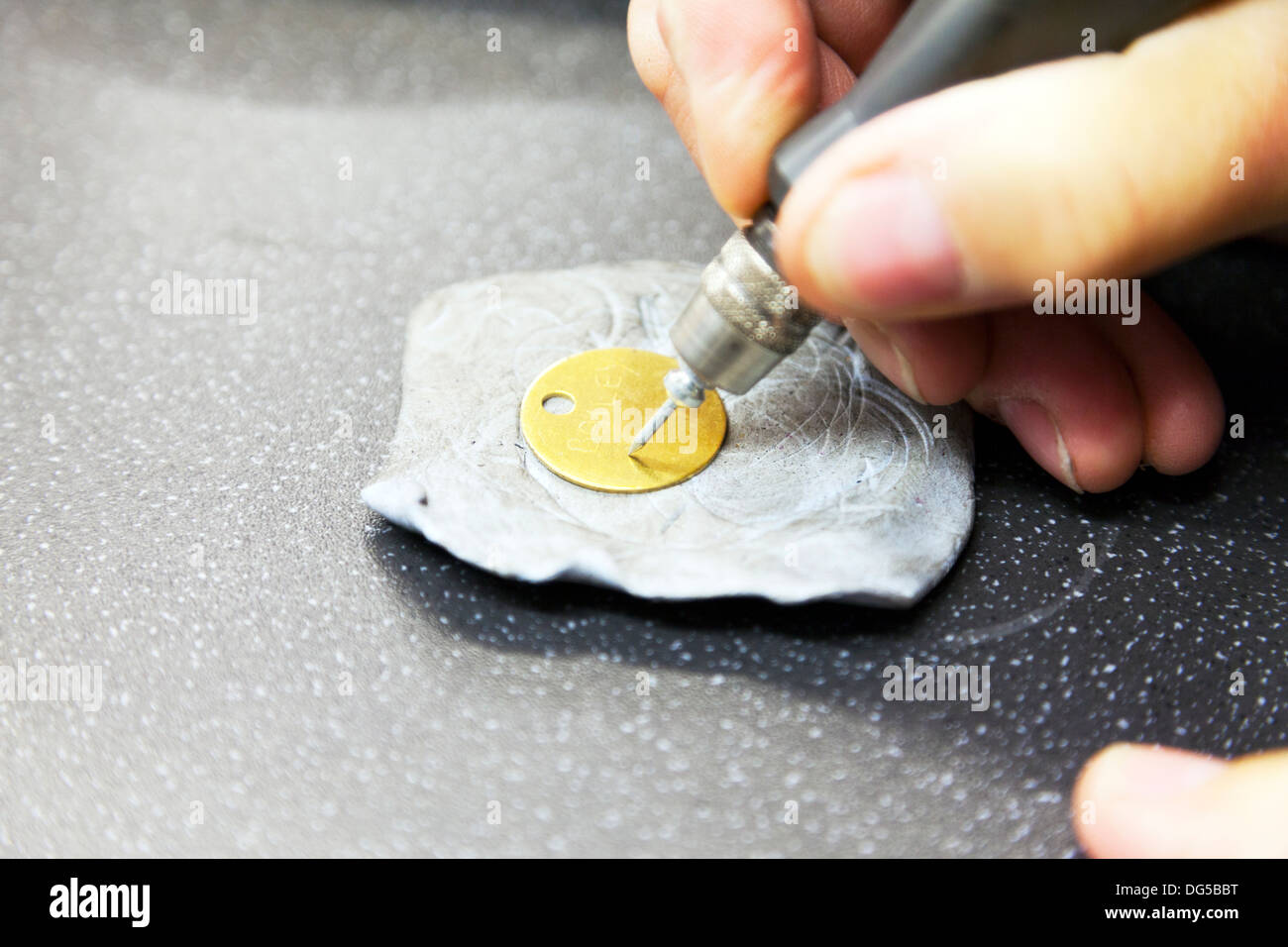 Man engraving disc with hand held engraver engrave name on pet disc male working - Stock Image