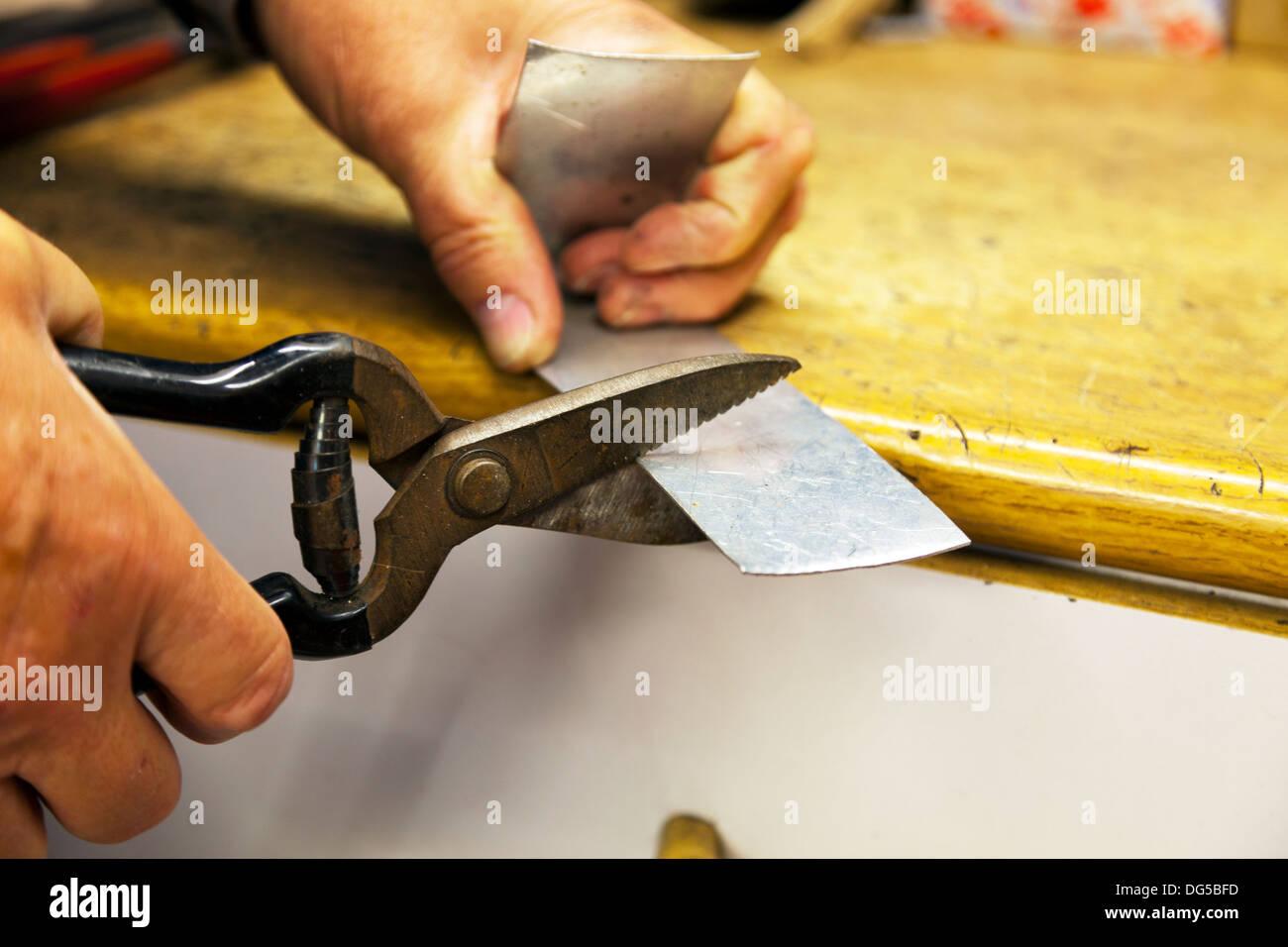 Mans hands cutting tin with tin snips cutters sheet tin Stock Photo