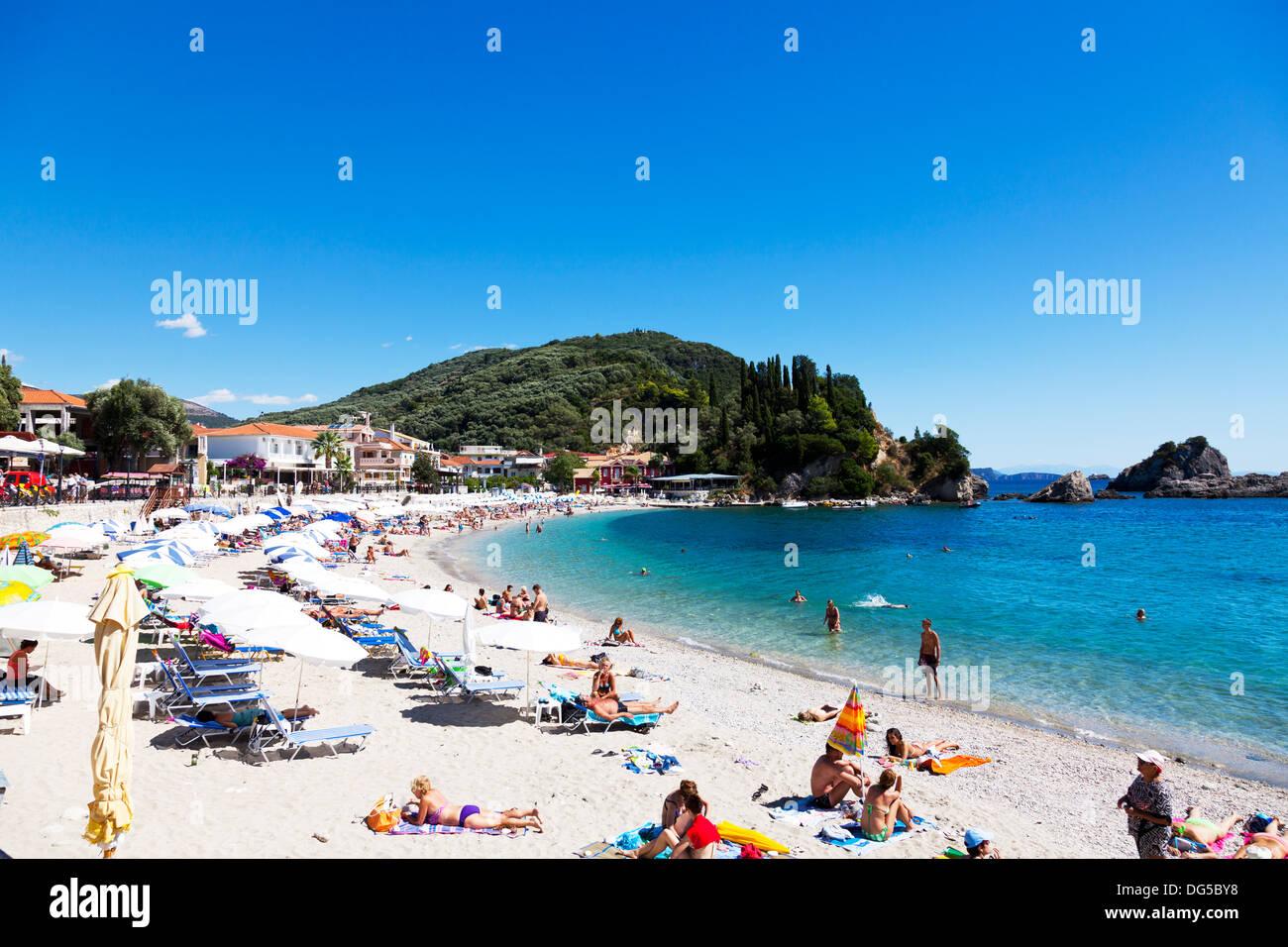 Parga town beach summer parasols sunbathers sun sunny tourists Greek Greece - Stock Image