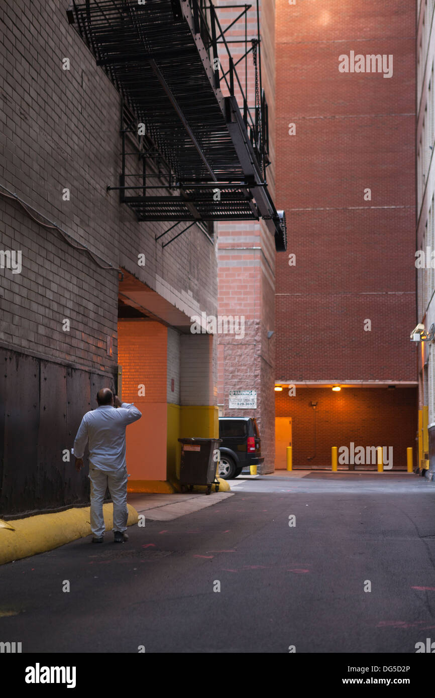 A man pauses to take a drink while in an alley in downtown Chicago. - Stock Image