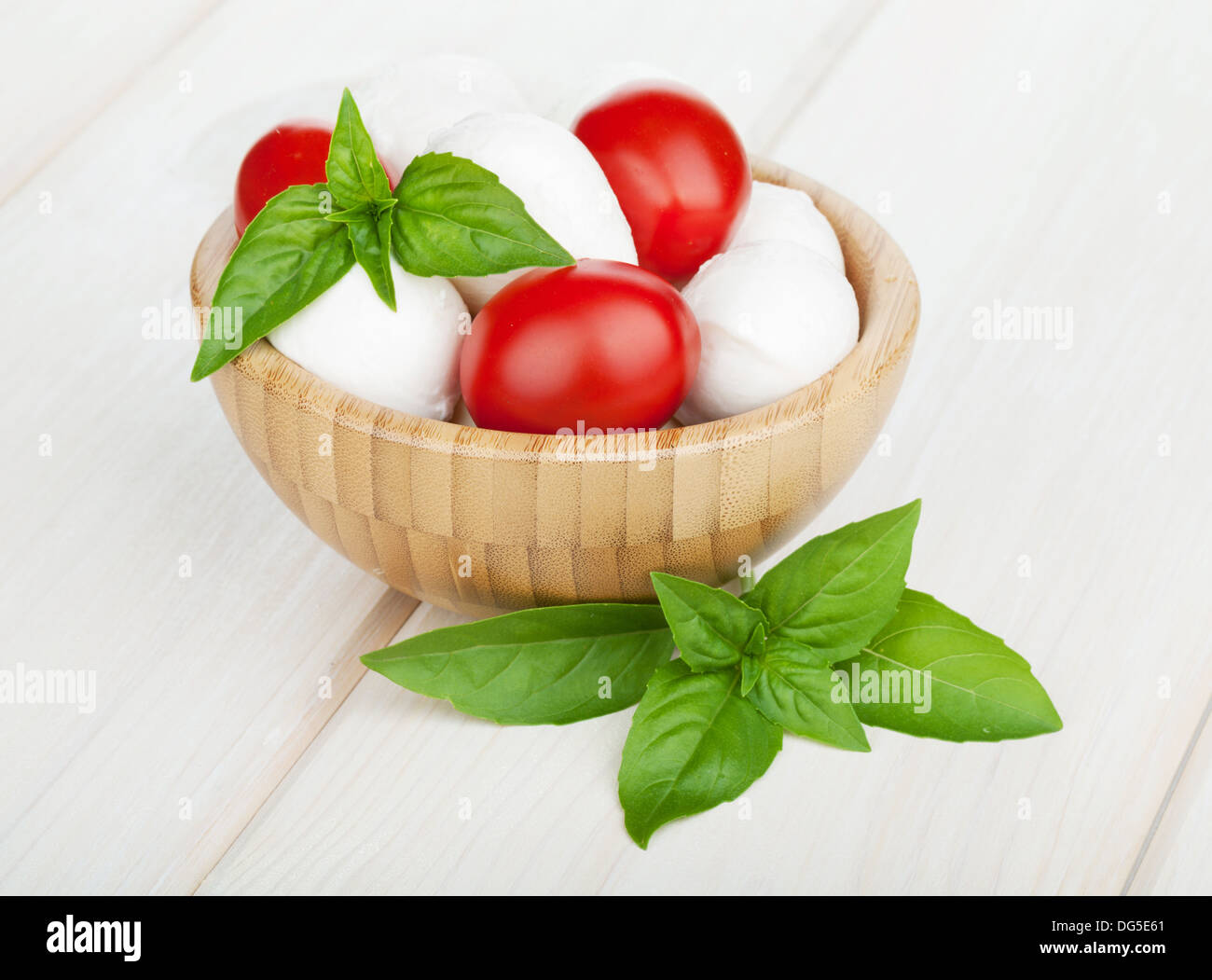 Mozzarella cheese with cherry tomatoes and basil on white wood table - Stock Image