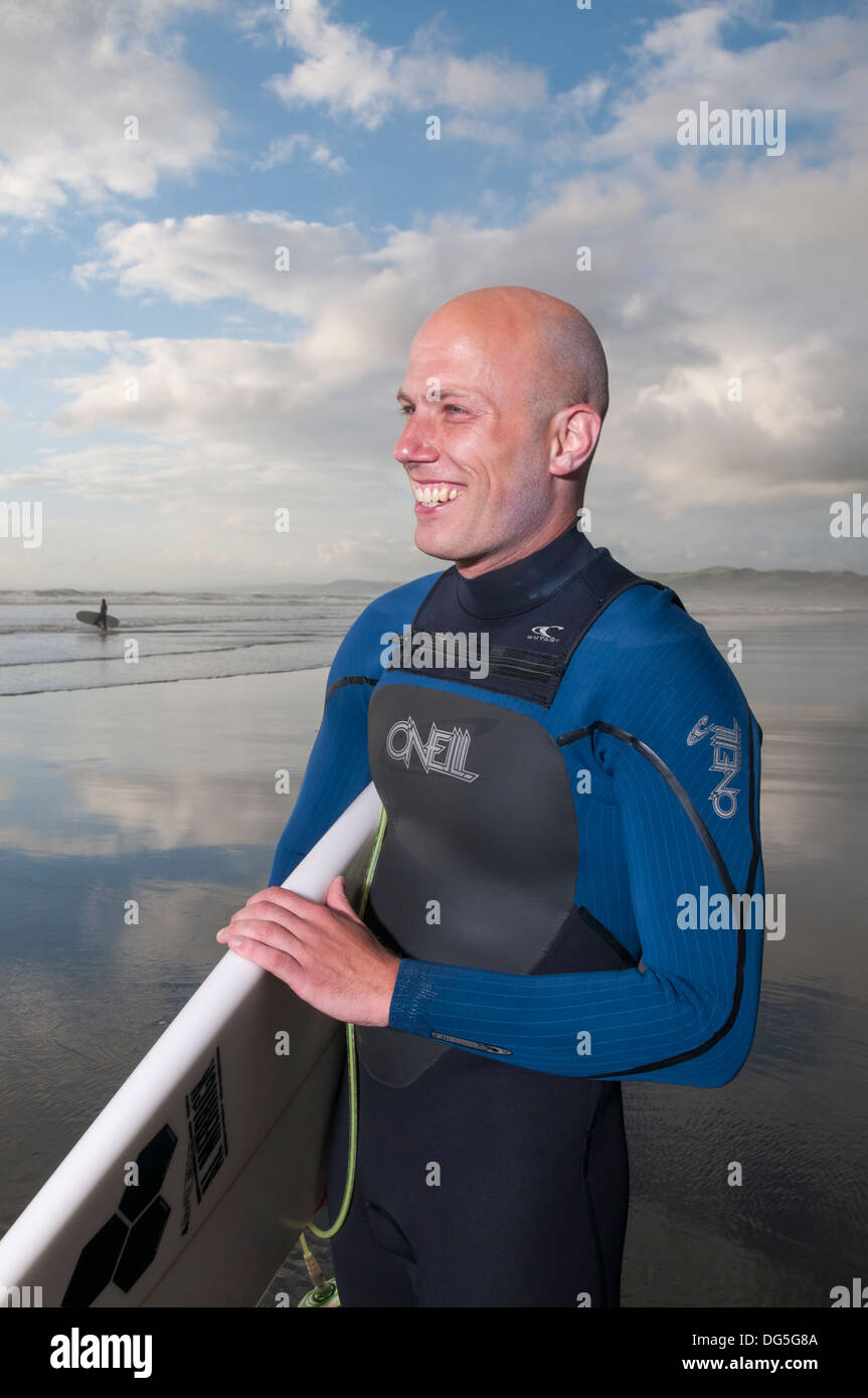 Bald man smiling holding surf board on beach with setting sun - Stock Image