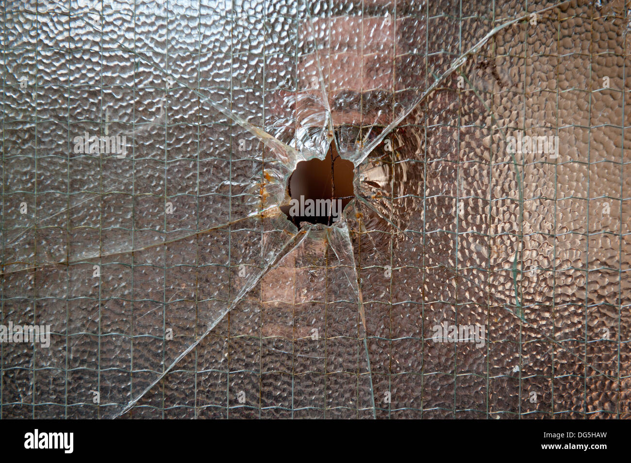 A hole on tome toughened glass that could have been caused by a bullet from a gun - Stock Image